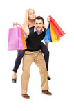 Młody człowiek daje piggyback przejażdżce kobieta z torba na zakupy obraz stock