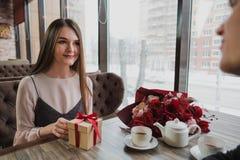 Młody człowiek daje prezentowi z czerwonym faborkiem dziewczyna, jego żona w kawiarni, okno obraz stock