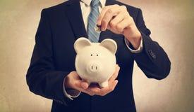 Młody człowiek deponuje pieniądze w prosiątko banku Zdjęcia Royalty Free