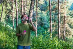 Młody człowiek Dmucha mydlanych bąble Mężczyzna w lato lesie w moun Obraz Royalty Free
