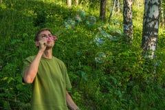 Młody człowiek Dmucha mydlanych bąble Mężczyzna w lato lesie w moun Obrazy Stock