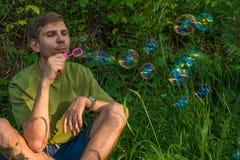 Młody człowiek Dmucha mydlanych bąble Mężczyzna w lato lesie w moun Zdjęcie Stock
