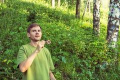 Młody człowiek Dmucha mydlanych bąble Mężczyzna w lato lesie w moun Fotografia Stock