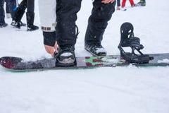 Młody człowiek dociska patki na jego snowboard Obraz Royalty Free