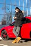 Młody człowiek dzwoni blisko nowożytnego sportowego samochodu zdjęcia stock
