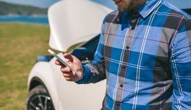 Młody człowiek dzwoni wiszącą ozdobą z łamanym puszka samochodem zdjęcia royalty free