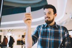 Młody człowiek ekranizacja coś na jego telefonie komórkowym na miastowym tle zdjęcie stock