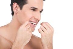 Młody człowiek flossing jego zęby odizolowywających na białym tle Fotografia Royalty Free