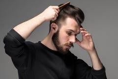 Młody człowiek grępla jego włosy fotografia royalty free