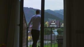 Młody Człowiek iść od jego pokoju balkon z szkłem wino, spojrzenia przy górami zbiory