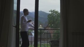 Młody Człowiek iść od jego pokoju balkon z szkłem wino, spojrzenie przy górami zbiory wideo