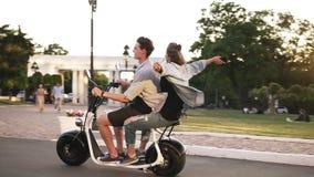 Młody człowiek i jej dziewczyna jedziemy elektryczną żółć w crowdy zieleń parku Być ubranym przypadkowy szczęśliwe chwile zdjęcie wideo
