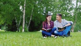 Młody człowiek i kobieta czyta książkę w parku Siedzą na zielonym gazonie zbiory