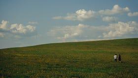 Młody człowiek i kobieta ma zabawę na wsi łące z ziele i kwiatami Obrazy Stock