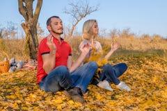 Młody człowiek i kobieta medytuje w jesień parku obraz royalty free