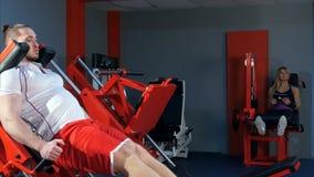 Młody człowiek i kobieta z pastylką robi nóg ćwiczeniom w gym Obrazy Royalty Free