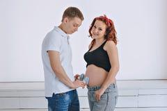 Młody człowiek i młoda piękna kobieta patrzeje each inny W oczekiwaniu na dziecko Ciężarna miedzianowłosa kobieta Fotografia Royalty Free