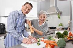 Młody człowiek i stara kobieta gotuje wpólnie w kuchni obraz stock