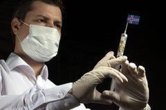 Młody człowiek jako lekarka daje medycznemu zastrzykowi Islandzka flaga obrazy stock