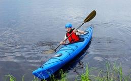 Młody człowiek jazda wokoło jeziora na kajaku Zdjęcia Royalty Free