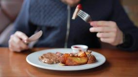 Młody człowiek je apetycznego stek z grulami i kumberlandem w kawiarni zdjęcie wideo
