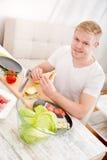 Młody człowiek je kanapkę w domu fotografia royalty free
