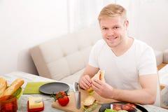 Młody człowiek je kanapkę w domu zdjęcie stock