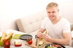 Młody człowiek je kanapkę w domu zdjęcie royalty free