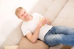 Młody człowiek je kanapkę w domu fotografia stock
