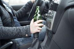 Młody człowiek jedzie jego samochód podczas gdy pijący alkohol obraz royalty free