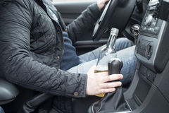 Młody człowiek jedzie jego samochód podczas gdy pijący alkohol zdjęcie royalty free