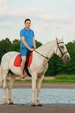 Młody człowiek jedzie konia przy zmierzchem na plaży Mężczyzna z hors Zdjęcie Stock