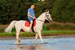 Młody człowiek jedzie konia przy zmierzchem na plaży Mężczyzna z hors Fotografia Stock