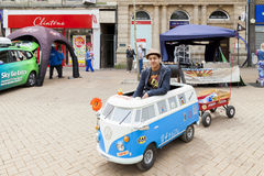 Młody człowiek jedzie miniaturowego wolkswagena obozowicza samochód dostawczego zdjęcia stock