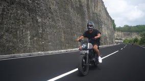 Młody człowiek jedzie na obyczajowym motocyklu na pięknej drodze zbiory wideo