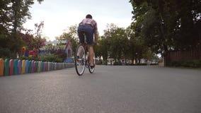 Młody człowiek jedzie rocznika bicykl przy aleją park Sporty faceta jeździć na rowerze plenerowy z słońce połyskiem przy tłem zbiory