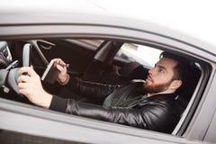 Młody człowiek jedzie samochód z żelazną kolbą obrazy stock