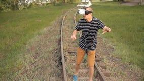 Młody człowiek jest na poręczach dla sztachetowego transportu w rzeczywistość wirtualna hełmie Widoków wizerunki, wideo gry Świat zbiory