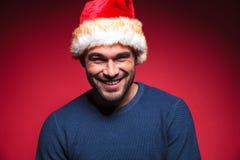 Młody człowiek jest ubranym czerwony Santa kapeluszu ono uśmiecha się Zdjęcia Royalty Free