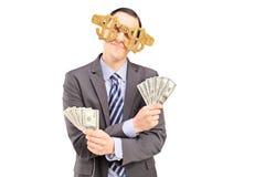 Młody człowiek jest ubranym dolarowego znaka szkła i trzyma USA dolary Obrazy Stock