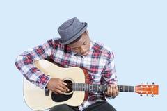 Młody człowiek jest ubranym kapelusz jako bawić się gitarę nad bławym tłem Obraz Royalty Free