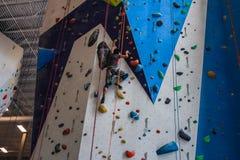 Młody człowiek jest ubranym kolorowego ubraniowego pięcie na wspinaczkowej ścianie indoors fotografia royalty free