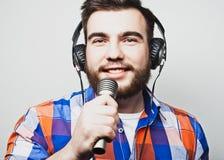 Młody człowiek jest ubranym koszulowego mienia z brodą mikrofon Zdjęcie Stock