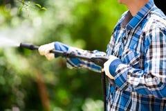 Młody człowiek jest ubranym kwadrata mienia wysokości deseniowego błękitnego naciska wodnego pistolet na ogrodowym tle, Obrazy Stock