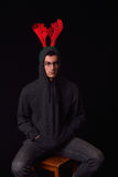 Młody człowiek jest ubranym renifera uzbrajać w rogi na jego czarnym hoodie z śmiesznym Zdjęcia Stock