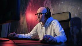 Młody człowiek jest ubranym słuchawki i początek grę online z jego przyjaciółmi Męski gamer uśmiecha się grę online na komputerze zdjęcie wideo