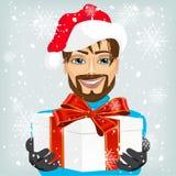 Młody człowiek jest ubranym Santa kapelusz oferuje prezent royalty ilustracja