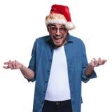 Młody człowiek jest ubranym Santa kapelusz patrzeje bardzo wprawiać w zakłopotanie Obrazy Royalty Free