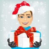 Młody człowiek jest ubranym Santa ofiary kapeluszowego prezent ilustracji