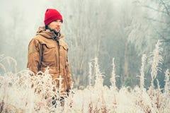 Młody Człowiek jest ubranym zimy kapeluszowy ubraniowy plenerowego z mgłową lasową naturą na tło podróży zdjęcia royalty free